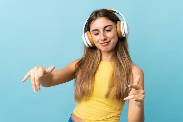 Młoda kobieta nad odosobnioną błękit ściany słuchającą muzyką i tanem