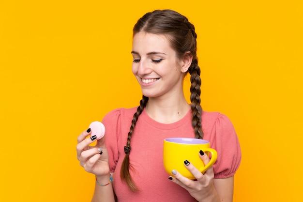 Młoda kobieta nad odosobnioną kolor żółty ścianą trzyma kolorowych francuskich macarons i filiżankę mleka