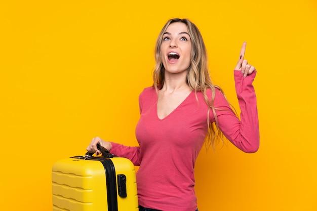 Młoda kobieta nad odosobnioną kolor żółty ścianą w wakacje z podróży walizką i wskazywać up