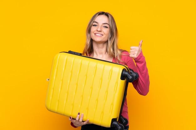 Młoda kobieta nad odosobnioną kolor żółty ścianą w wakacje z podróży walizką z kciukiem up i