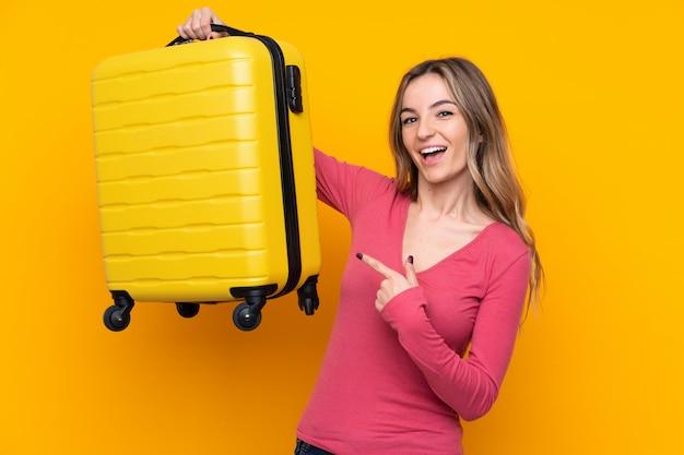 Młoda kobieta nad odosobnioną kolor żółty ścianą w wakacje z podróży walizką
