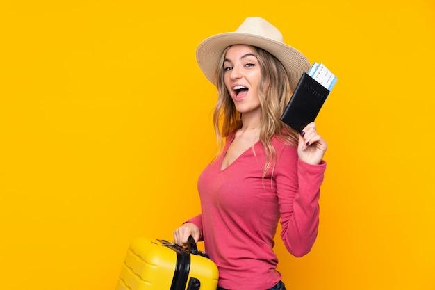 Młoda kobieta nad odosobnioną kolor żółty ścianą w wakacje z walizką i paszportem