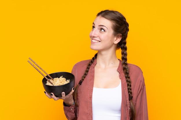 Młoda kobieta nad odosobnioną kolor żółty ściany przyglądającym up podczas gdy ono uśmiecha się podczas gdy trzymający puchar kluski z chopsticks