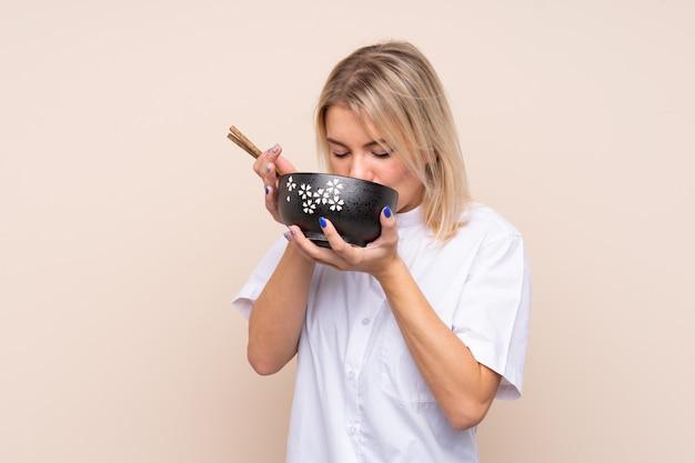Młoda kobieta nad odosobnioną ścianą trzyma puchar kluski z pałeczkami i je je