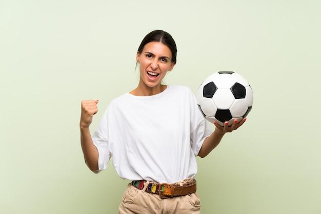 Młoda kobieta nad odosobnioną zieleni ścianą trzyma piłki nożnej piłkę