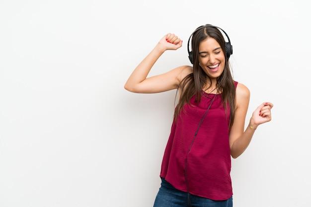 Młoda kobieta nad odosobnionym białym słuchaniem muzyka z hełmofonami