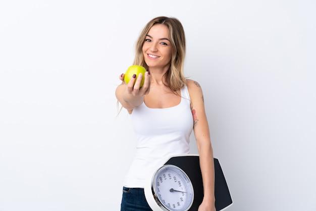 Młoda kobieta nad odosobnionym biel ściany mieniem waży maszynę i oferuje jabłka