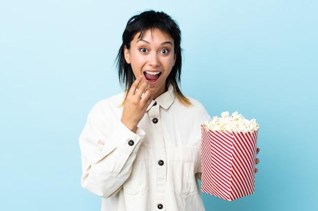 Młoda kobieta nad odosobnionym błękitem trzyma dużego wiadro popcorns