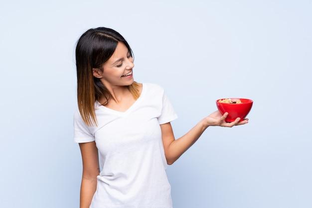 Młoda kobieta nad odosobnionym błękitem trzyma puchar zboża