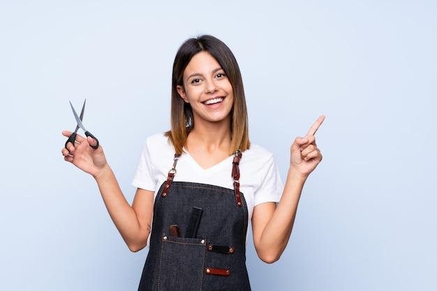 Młoda kobieta nad odosobnionym błękitem z fryzjera lub fryzjera męskiego suknią i wskazywać stronę
