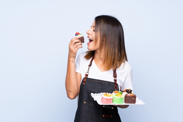 Młoda kobieta nad odosobnionym błękitnym trzyma mini ciastkami i je je