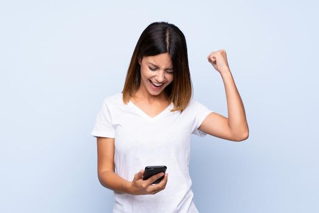 Młoda kobieta nad odosobnionym błękitnym używa telefonem komórkowym