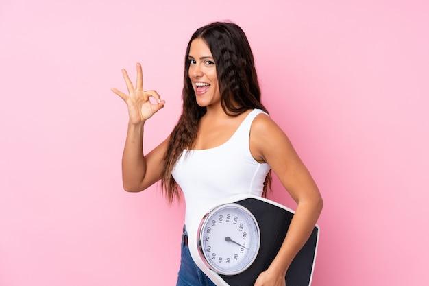 Młoda kobieta nad odosobnionym różowym mieniem waży maszynę i robi ok znakowi