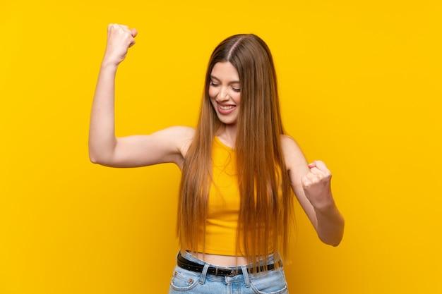 Młoda kobieta nad odosobnionym żółtym tłem świętuje zwycięstwo