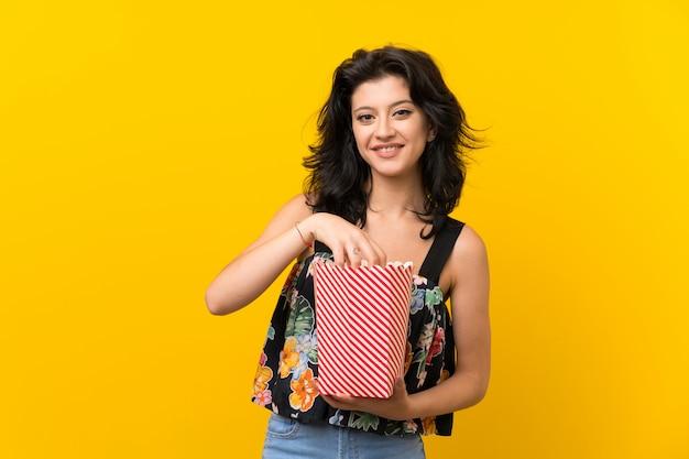 Młoda kobieta nad odosobnionym żółtym tłem trzyma puchar popcorns