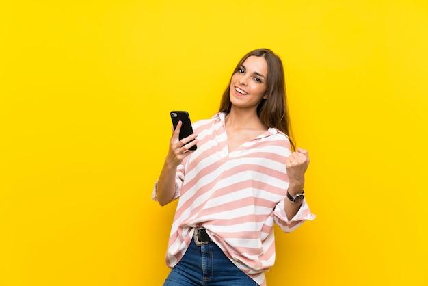 Młoda kobieta nad odosobnionym żółtym tłem z telefonem w zwycięstwo pozyci