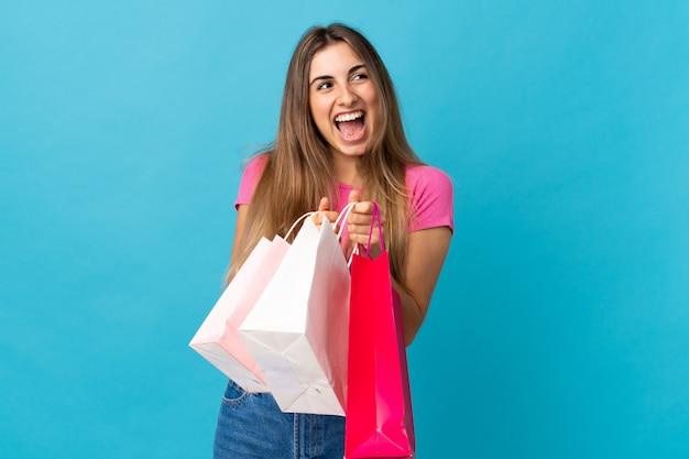 Młoda kobieta nad odosobnionymi błękit ściany mienia torba na zakupy i zaskakujący