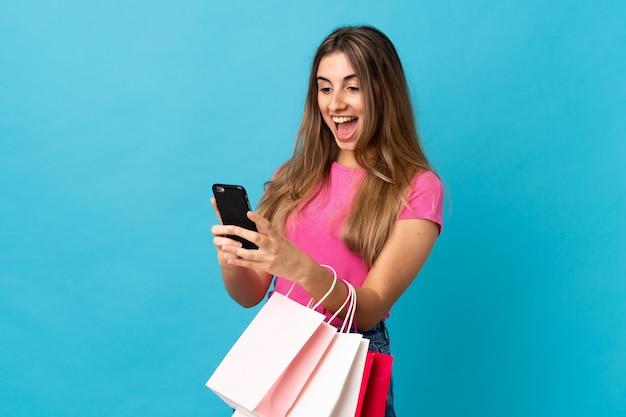 Młoda kobieta nad odosobnionymi błękit ściany ścianą trzyma torba na zakupy i pisze wiadomości z jej telefonem komórkowym przyjaciel