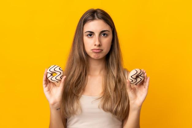 Młoda kobieta nad odosobnionymi kolor żółty ściany mienia donuts z smutnym wyrażeniem