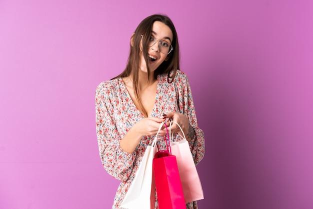 Młoda kobieta nad odosobnionymi purpurami izoluje mień torba na zakupy i zaskakujący