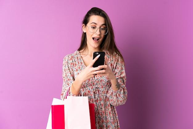Młoda kobieta nad odosobnionymi purpurami izoluje mienia torba na zakupy i pisać wiadomości z jej telefonem komórkowym przyjaciel