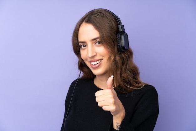 Młoda kobieta nad odosobnionymi purpurami izoluje słuchającą muzykę z kciukiem up i