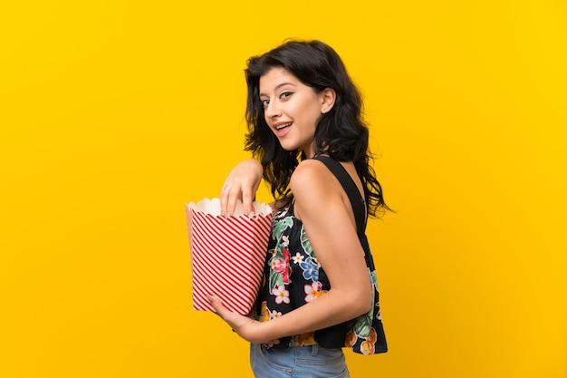 Młoda kobieta nad odosobnionymi żółtymi tła łasowania popkornami