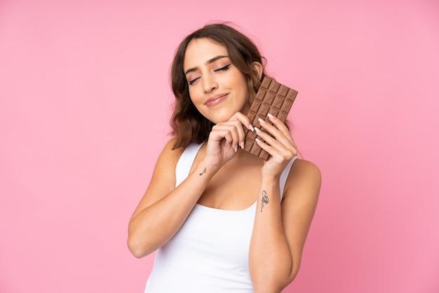 Młoda kobieta nad różową ścianą bierze czekoladową pastylkę i szczęśliwa