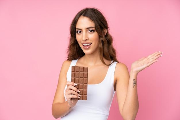 Młoda kobieta nad różową ścianą bierze czekoladową pastylkę i zaskakuje
