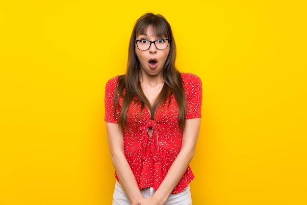 Młoda kobieta nad żółtą ścianą z niespodzianką wyraz twarzy