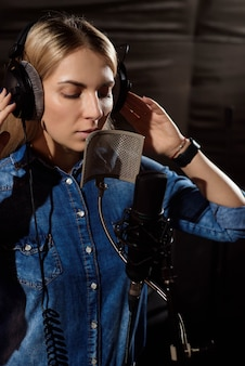 Młoda kobieta nagrywa piosenkę w studiu.