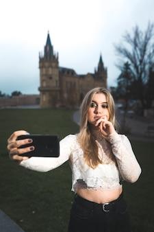 Młoda kobieta nagrywa się telefonem komórkowym na ulicy.