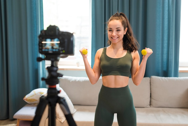 Młoda kobieta nagrywanie sesji treningowej w domu