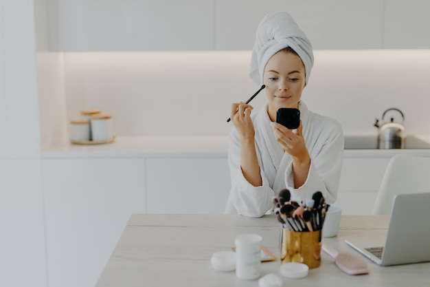 Młoda kobieta nakłada kosmetyki do makijażu pędzlem przed lustrem