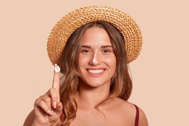 Młoda kobieta nakłada krem z filtrem przeciwsłonecznym na twarz i pokazuje palec z filtrem przeciwsłonecznym, model pozuje na beżu, stoi na ścianie studia z wyśmienicie uśmiechem, ubrana w kostium kąpielowy.