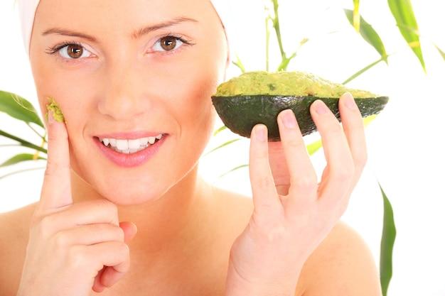 Młoda kobieta nakłada na twarz naturalną maskę z awokadoado