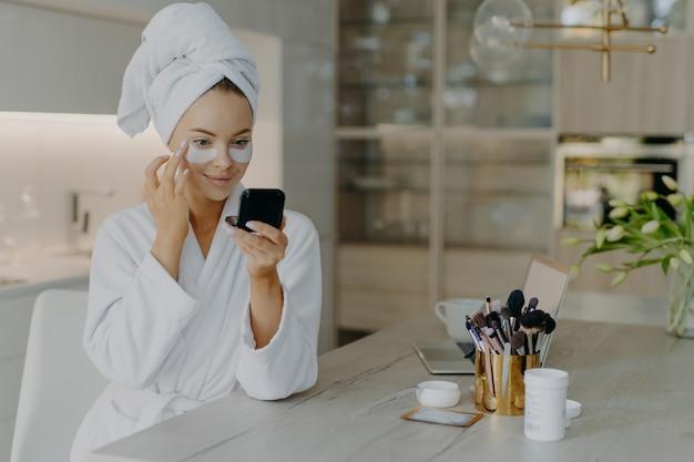 Młoda kobieta nakłada plastry kosmetyczne patrzy na siebie w lustrze