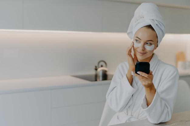 Młoda kobieta nakłada plastry kosmetyczne trzymając lustro