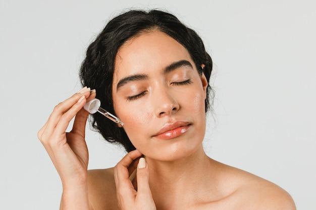 Młoda kobieta nakłada serum na twarz