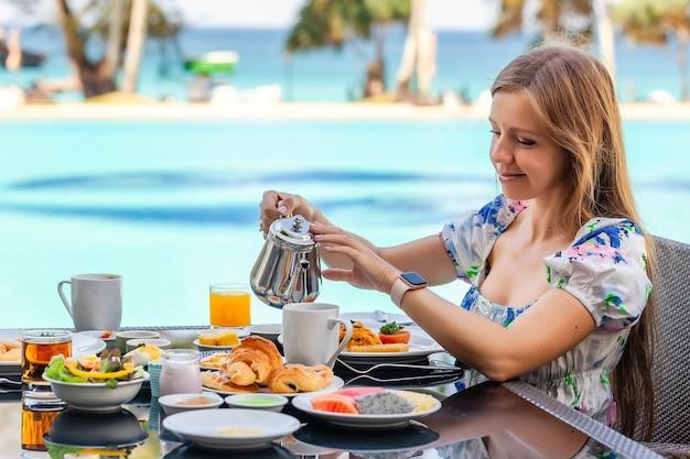 Młoda kobieta nalewa herbatę do filiżanki jeść śniadanie w restauracji przy basenie