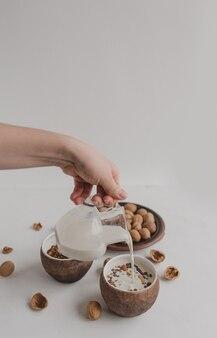 Młoda kobieta nalewa mleko do miski z muesli. ręka trzyma śmietankę, dzbanek mleka. zdrowe śniadanie muesli, płatków owsianych, płatków śniadaniowych, orzechów.