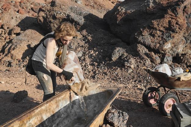 Młoda kobieta nalewa wodę ze zbiornika do dużego pojemnika na pustyni