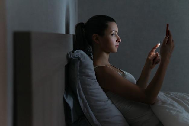 Młoda kobieta nałogowo używa swojego smartfona do rozmów w łóżku do późnych godzin nocnych