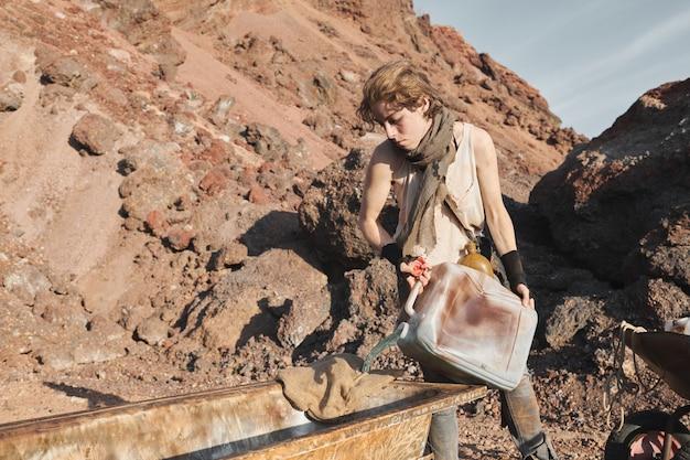 Młoda kobieta napełniająca brudną wannę wodą ze zbiornika podczas pracy na pustyni