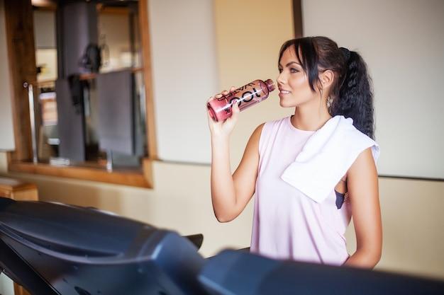 Młoda kobieta napój czysta woda w siłowni fitness