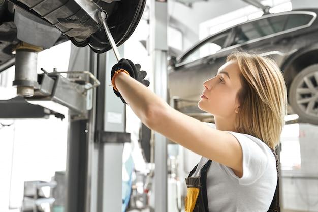 Młoda kobieta naprawia podwozie samochodu w serwisie samochodowym.