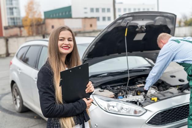 Młoda kobieta naprawia samochód z schowkiem i pracownikiem