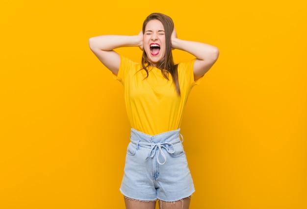 Młoda kobieta nastolatka na sobie żółtą koszulkę zakrywającą uszy rękami, starając się nie słyszeć zbyt głośnego dźwięku.