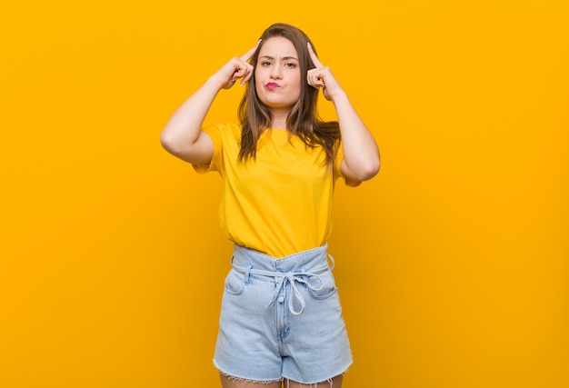 Młoda kobieta nastolatka w żółtej koszuli koncentruje się na zadaniu, trzymając palce wskazujące głową.