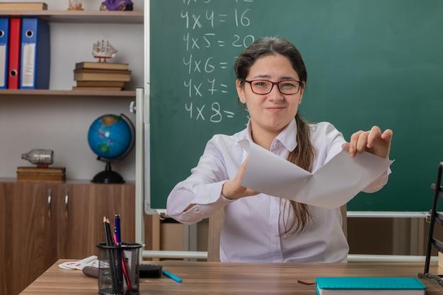 Młoda kobieta nauczyciel w okularach łzawienie kartkę papieru, patrząc niezadowolony siedzi